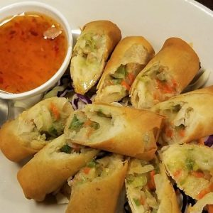 Deep fried egg rolls dip in Thai sweet and sour sauce.